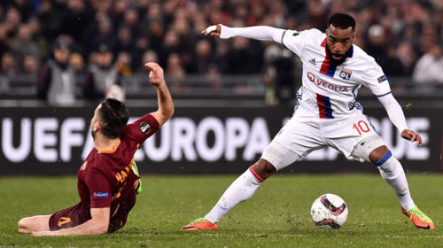 Alexandre Lacazette is challenged by Konstantinos Manolas