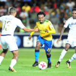 Percy Tau challenged by Reeve Frosler and Elias Pelembe