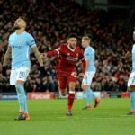 Players of ManCity react as Liverpool's Alex Oxlade-Chamberlain celebrates after scoring.