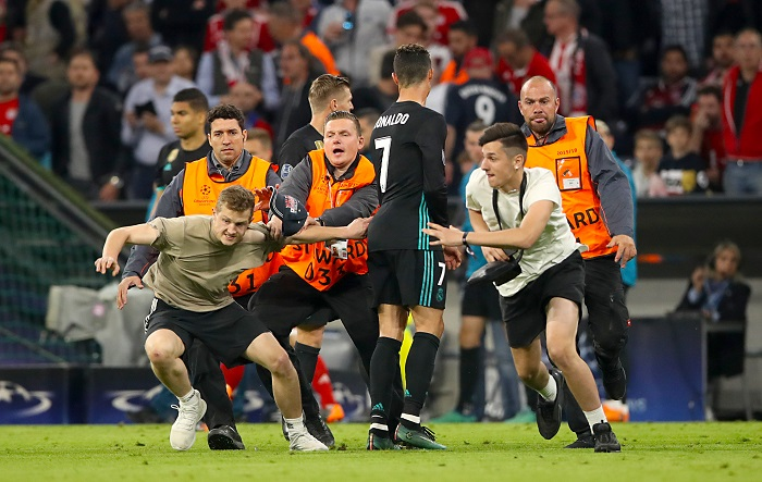 Pitch invaders are chased by stewards past Real Madrid's Cristiano Ronaldo after the final whistle.