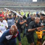Players, staff and officials run into the stadium to get away from the fan violence at the Moses Mabida Stadium.