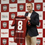 Spanish soccer player Andres Iniesta shows off his new jersey