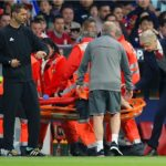 Arsenal manager Arsene Wenger speaks with Arsenal's Laurent Koscielny as he is stretchered off.