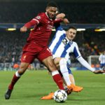 Liverpool's Joe Gomez and Diogo Dalot battle for the ball.