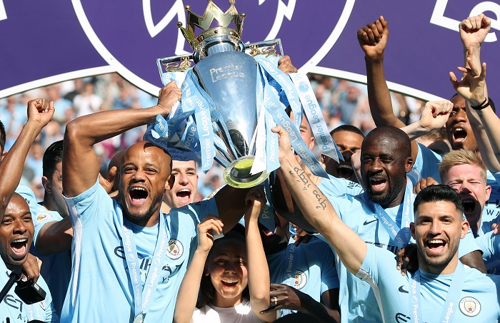 Manchester City's Vincent Kompany (left), Yaya Toure (second right) and Sergio Aguero lift the Premier League trophy.