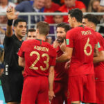 Players of Portugal argue with the referee after a controversial VAR decision.