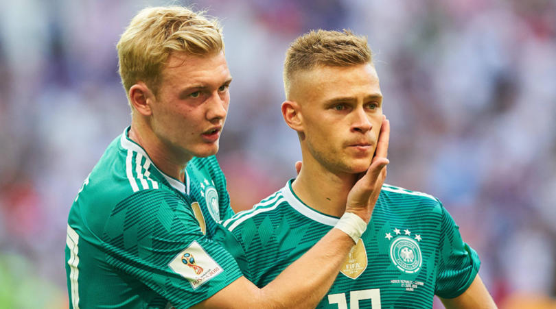 Joshua Kimmich consoled bu Julian Brandt after Germany's World Cup elimination.